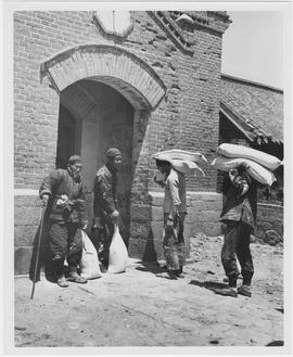Ten-pound bags of UNRRA flour are being taken into an old church in the village of Li Chuan near ...