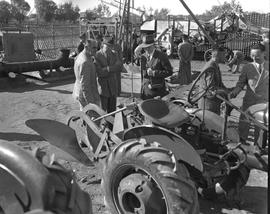 CNRRA / 711 Director-General Lowell W Rooks inspecting tractors at agricultural experimental farm...