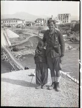 [Yugoslavia] At the blasted bridge-head near Podgorica stands a young Partisan warrior and his st...