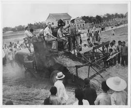While villagers watch, the first UNRRA combine in operation in China, a self-propelled Massey-Harris which threshes wheat in a single operation, goes into action in Honan Province