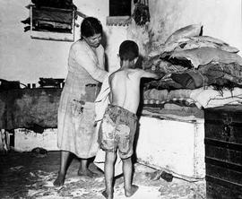 [Greece] Arete Arnotis and her son, Michael, prepare the tattered blankets for bedtime.