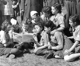 [Germany] : UNRRA 1944: Kaserne, Germany,  group of children read a Jewish newspaper as they awai...