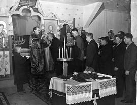 [Germany]: UNRRA / 3056 : Hersfeld, Germany, After the dedication ceremomy at the new chapel at the UNRRA DP center in Hersfeld, Germany, members of the congregation file past the priest to receive his blessings, be sprinkled with Holy Water and to kiss.