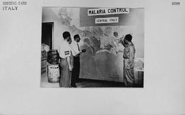 [Italy] In Planning Room at UNRRA Headquarters, Captain Lloyd Gebhard, Chief of UNRRA Malaria Control program, discusses completed operations (treated areas shaded on map), with engineers.
