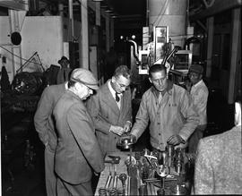 CNRRA / 732 UNRRA Director-General Lowell W Rooks inspects with interest spare machine parts manu...