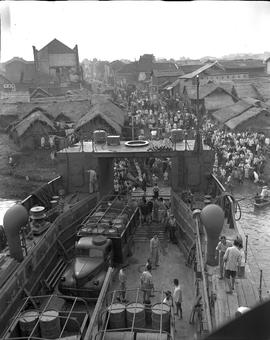 Trucks and gasoline are unloaded from a river barge at Changsha, capital of the famine-stricken p...