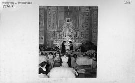 [Italy] American cast-off clothes are piled high in the chapel altars of the Church of Santa Croc...