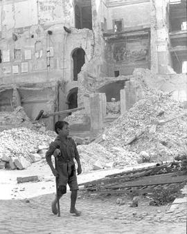 [Italy] A young victim of the war hobbles through the ruined streets of Cisterna, Italy on his home-made crutches.
