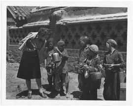 A tattered little boy of the village of Li Chuan shows Ann Cottrell of Richmond, Va, UNRRA China correspondent, how much flour he has scraped off the ground during the distribution by CNRRA of free UNRRA flour to the villagers