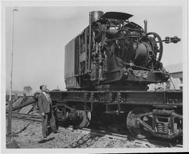 JF Tubbs, Chief of UNRRA's Railway Rehabilitation Program, surveys partly assembled American...