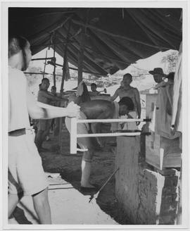Chinese village blacksmiths, idle during the war, at work again in Honan because of loans in cash...