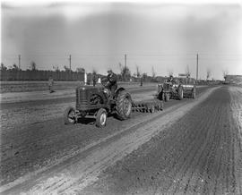 CNRRA / 715 Tractor operators drive UNRRA-supplied Allis Chalmers farm tractors at the agricultural experimental farm of the CNRRA-MOAF office at Point Island