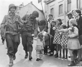 Citizens of Velfingen, Luxembourg, stand beside the road to cheer the entrance of their liberators