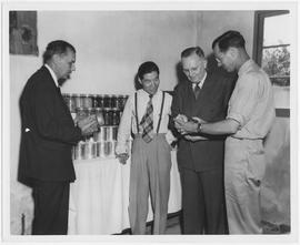 Hoyt Turner, right, UNRRA food processing specialist, shows William Green, head of UNRRA's a...