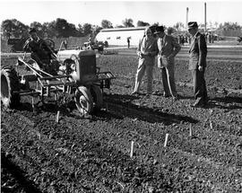 CNRRA / 710  Director-General Lowell W Rooks (center) watches an AMOMO-trained Chinese tractor operator drive an UNRRA-supplied Allis Chalmers farm tractor