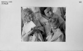 [Italy] Mother and two children waiting with case history cards in hand for physical examination ...