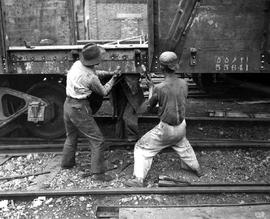 CNRRA / 459  Workmen at the Kowloon railroad yards assemble one of 3,445 freightcars supplied by ...