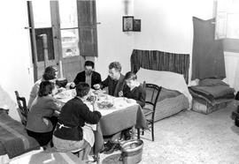 [Italy] D'Ambia family enjoying their noon meal, consisting of a broth with pasta, braised b...
