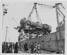 "A fully-assembled, 90-ton ""MacArthur"" type railroad locomotive is swung to the tracks a..."