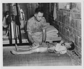 An UNRRA doctor administers blood plasma to a young starvation victim in China's Hunan famin...