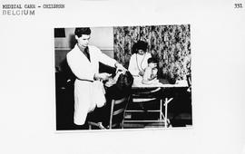 [Belgium] Drs. Devillers and Thomas, left to right, of the Belgium Red Cross, examining and treat...