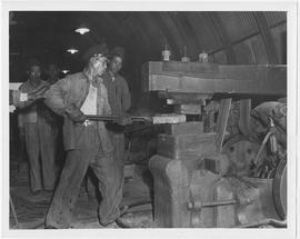 Hammersmith trainee at the National Agricultural Engineering Corporation's Central Shop, near Point Island, prepares to make a farm hoe from a heavy piece of block metal