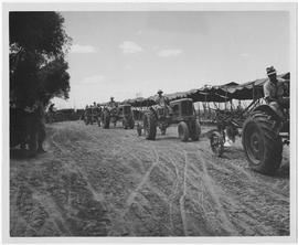 Farm tractors operated by newly trained Chinese peasant farmers leave the CNRRA-UNRRA Relief Plow...