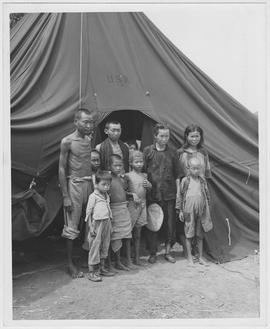 Emaciated famine refugees standing before one of 30 US Navy tents in a CNRRA-UNRRA camp -- one of seven in Hengyang, Hunan Province, each housing about 300 starving people