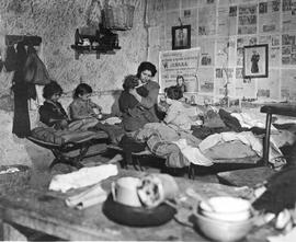 "[Italy] Victims of war far removed from light and air, this mother and her children, in one of the Naples caves, now put their simple faith in UNRRA and the promise on the poster on the wall: ""Food, health and hope"" [1945]"