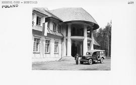 [Poland] An UNRRA ambulance in front of the former hunting lodge of Count Zamoyski, now converted...