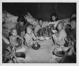 Country famine victims who poured into Hengyang at the rate of 50,000 in two months squat in one of 30 surplus US Navy tents in a CNRRA-UNRRA famine refugee camp in Hengyang, Hunan Province where they are housed after having been