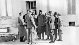 [Italy] Louis Varrichione (extreme left), Camps Administrator, talking to Abyssinian refugees at Leuca.