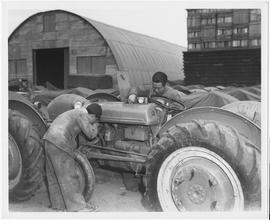 Students at the experimental farm of the CNRRA-MOAF office, Point Island, [examine] tractor machinery
