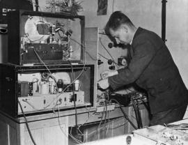 [Germany]: UNRRA / 3050 : Berchlesgaden, Germany, Richards Harjese, head of the camp communication section, and formerly an engineer with the Latvia V.E.R. ( State  Electro-Technical ) is shown checking the broadcast apparatus in the centers midget radio