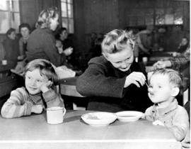 [Germany]: UNRRA / 3058 : Hohenfels, Germany, Hohenfels bay kitchen.  Shows an older girl feeding...